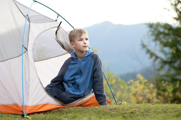 행복한 등산객 소년은 아름다운 여름 자연의 전망을 즐기며 산 캠프장의 관광 텐트에서 쉬고 있습니다.