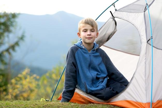 산악 야영장의 관광 텐트에서 쉬고 있는 행복한 등산객 소년 프리미엄 사진