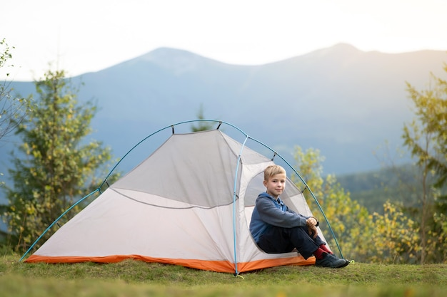 Happy hiker child boy resting in a tourist tent at mountain campsite enjoying view of beautiful summer nature.