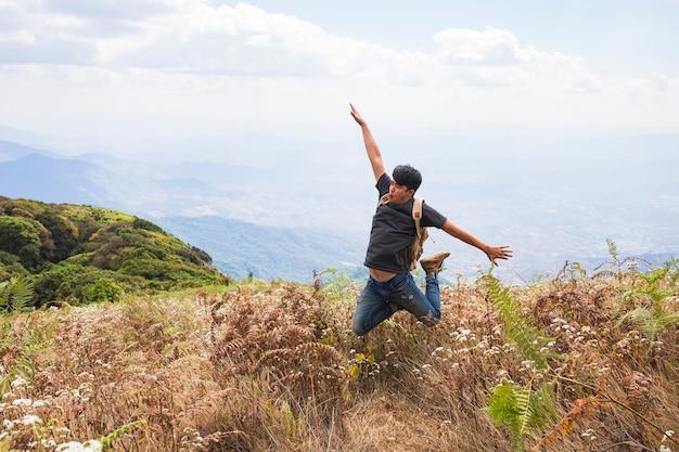 Happy hiker jumping in fields