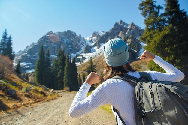 山道を歩いている幸せなハイカー。天山山脈の旅。
