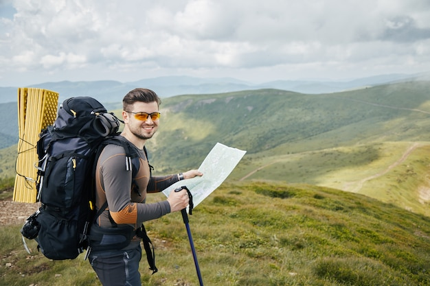 Happy hiker with big backpack holding map and smiling