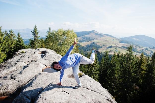 空中に手を置いて幸せなハイカーが岩の上に立っています。岩だらけの谷を見渡せます。