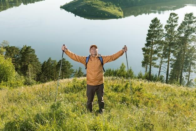 Happy hiking success. backpacker man raised hands enjoying nature.