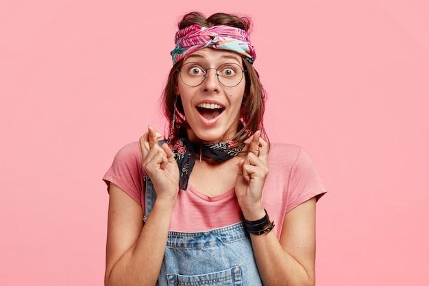 幸せなヒッピーの女性は前向きな表情で指を交差させ、スタイリッシュなヘッドバンドを着用し、夢が叶うことを強く望んでおり、カジュアルなtシャツとデニムのオーバーオールを着用し、ピンクの壁にポーズをとっています