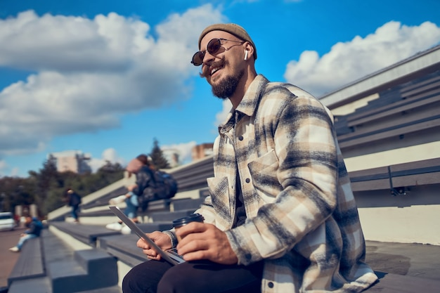 Счастливый хипстерский блогер в стильных очках набирает текст для привлечения новых подписчиков на свой сайт