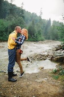 Счастливые пары битника целуя и обнимая около реки в горе. туристическая пара