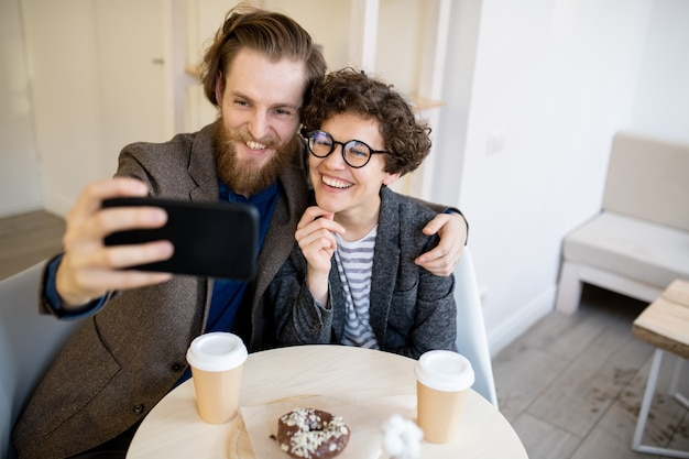 Happy hipster couple taking selfie in cafe