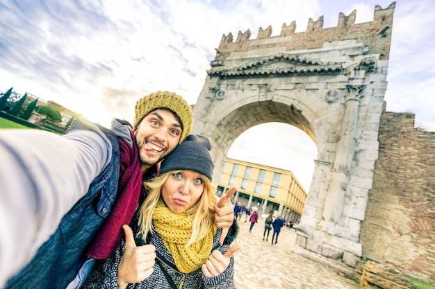 Happy hipster couple taking selfie at european city trip on winter clothes