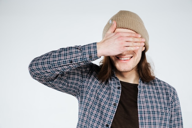 Happy hipster covering his eyes