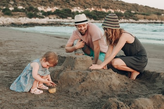 Happy hipster family at the beach building sand castle