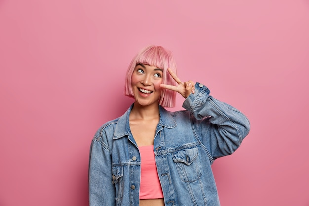 幸せな流行に敏感な女の子はピンクの髪をして勝利のジェスチャーをし、笑顔で成功を喜び、前向きな見方を表現し、夢のような表情をし、ファッションの服を着ています。スタイリッシュな女性が指でvサインを作る
