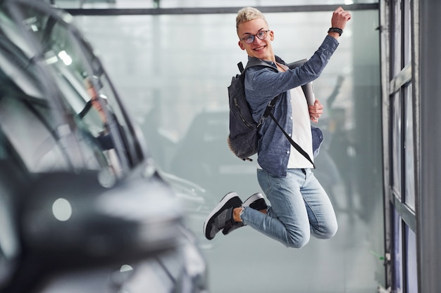 Happy hipster guy jumping indoors and near car
