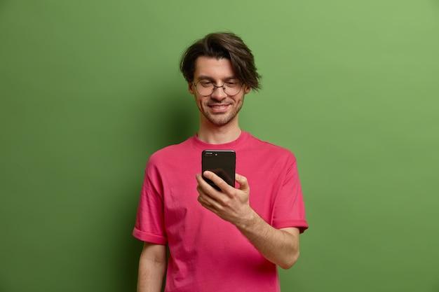 幸せな流行に敏感な男は携帯電話アプリケーションを使用しています