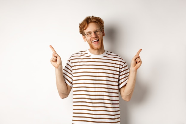 Happy hipster guy with red messy hair and glasses smiling, pointing fingers up, showing sale promotion, white background.