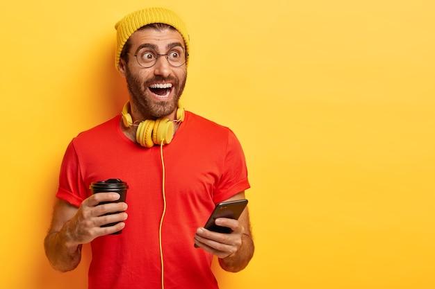 カジュアルな服装で幸せなヒップスターは、コーヒーカップと携帯電話を保持します