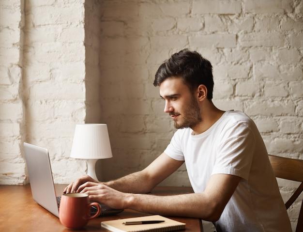 흰색 티셔츠에 행복 힙 스터는 테이블 아래에 앉아 여자 친구를위한 노트북 메시지에 입력