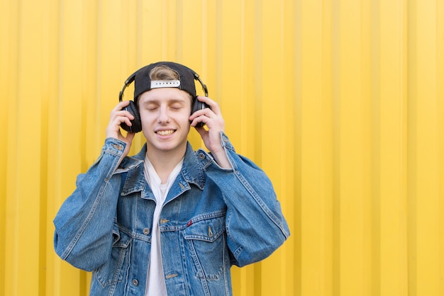 Happy hipster listens to music in headphones with closed eyes on a yellow wall.