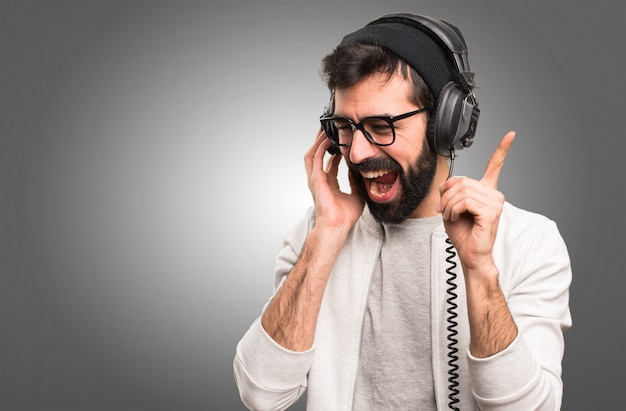 Happy hipster man listening music on grey background