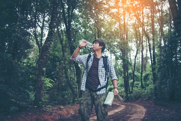 Happy hipster man tourist with backpack drinking water while hiking in nature forest.