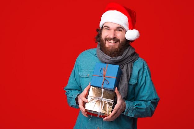 크리스마스 모자를 쓰고 행복 hipster 남자는 카메라에 웃 고 몇 가지 선물을 들고.