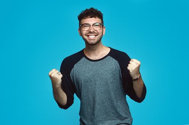 Счастливый хипстерский мужчина с бородой в повседневной одежде и очках ликует на синем фоне