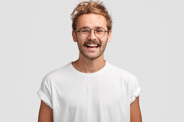 歯を見せる笑顔で幸せな流行に敏感な男、カジュアルな白いtシャツとメガネを着用