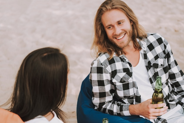 Happy hipster man and woman talk at beach party