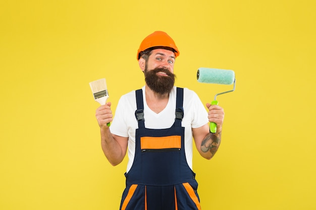 Happy hipster in safety helmet and work uniform hold paint roller and brush for decorating and painting under construction yellow background, painter.