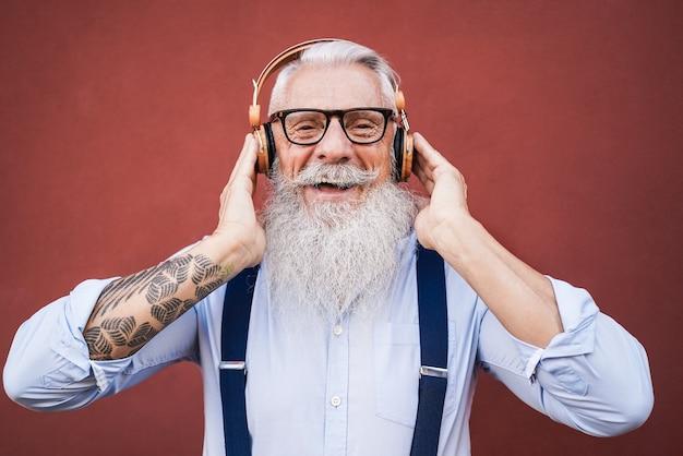 야외에서 재생 목록 음악을 듣고 행복 힙 스터 수석 남자-얼굴에 초점