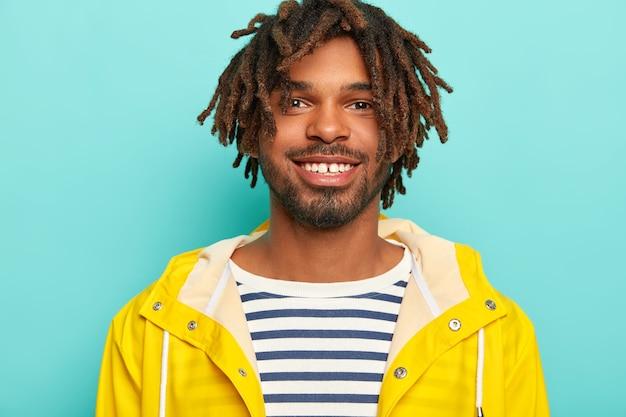 Felice hipster sorride piacevolmente, mostra i denti bianchi, indossa un maglione a righe e un impermeabile giallo, felice di avere un giorno libero, cammina durante la giornata autunnale, isolato sul muro blu