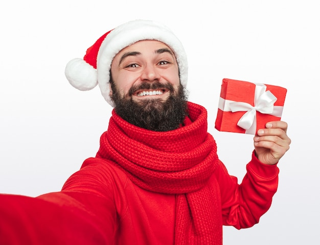 Happy hipster taking selfie with christmas gift