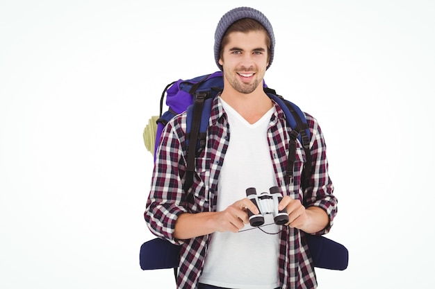 Happy hipster wearing backpack holding binoculars