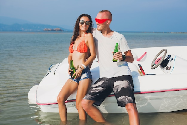 Happy hipster woman and man drinking beer on summer tropical vacation in thailand traveling on boat in sea, party on beach, people having fun together, positive emotions