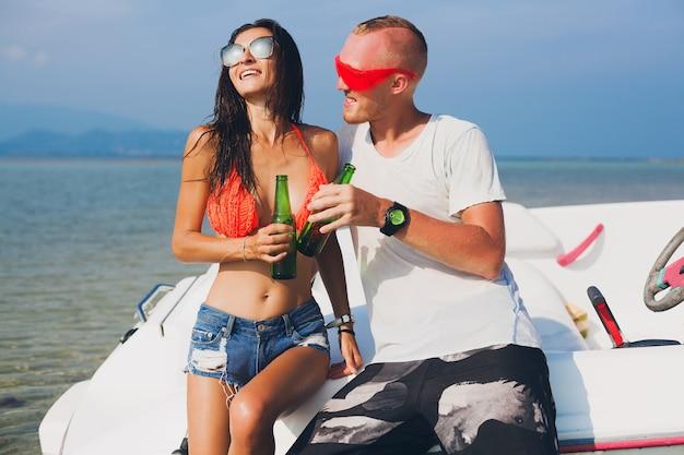 Felice hipster donna e uomo che beve birra in vacanza tropicale estiva in thailandia che viaggiano in barca in mare, festa sulla spiaggia, persone che si divertono insieme, emozioni positive