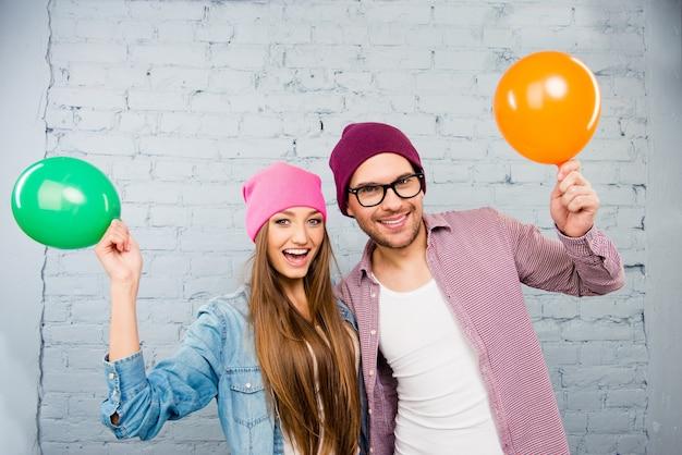 Счастливый битник молодой мужчина и женщина празднуют с воздушными шарами