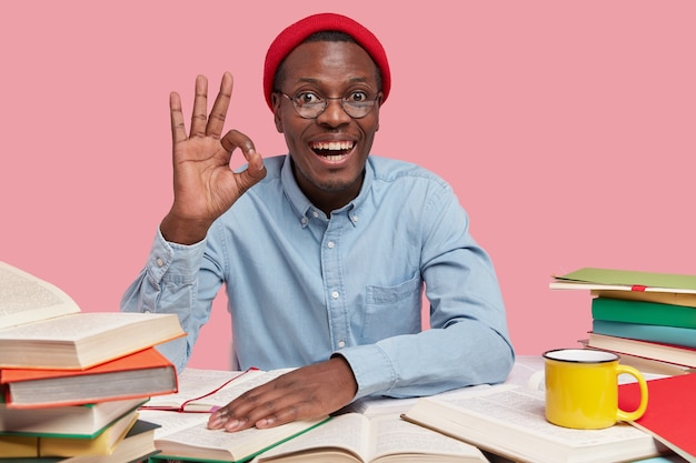 Happy hiptser with dark skin, joyful expression, dressed in elegant shirt, red hat, spectacles, makes okay gesture, confirms everything is fine, sits at desktop