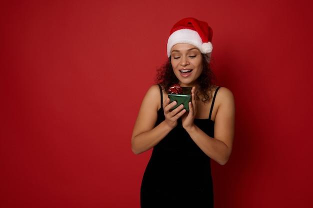 행복한 히스패닉계 아름다운 여성이 손에 든 작고 아름다운 크리스마스 선물 상자를 보고 행복을 느끼고 빨간색 배경 위에 광고 복사 공간이 있습니다. 새 해와 메리 크리스마스 개념입니다.