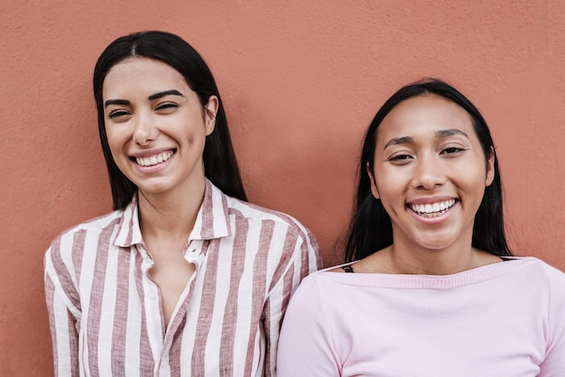 행복한 히스패닉계 소녀들이 카메라 앞에서 웃고 있는 것을 즐기고 - 오른쪽 여성의 얼굴에 초점을 맞춥니다
