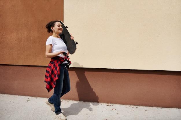 色付きの壁に音楽を聴いて通りを歩いて肩に木製のスケートボードを持って幸せなヒスパニック系の女性