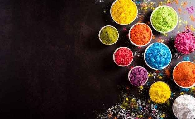 Happy holi festival decoration.top view of colorful holi powder on dark background