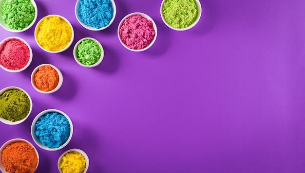 Happy holi festival decoration.top view of colorful holi powder on purple  background