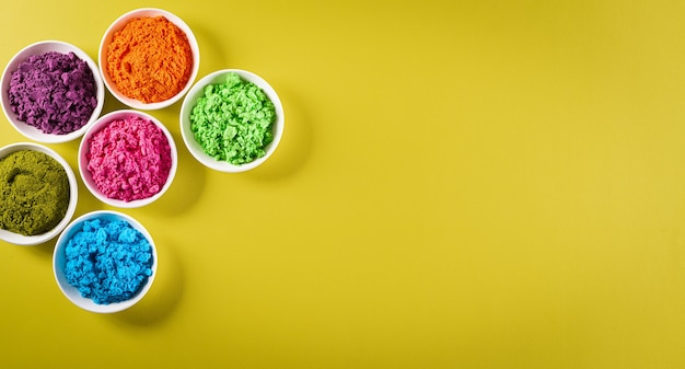 Happy holi festival decoration.top view of colorful holi powder on yellow  background
