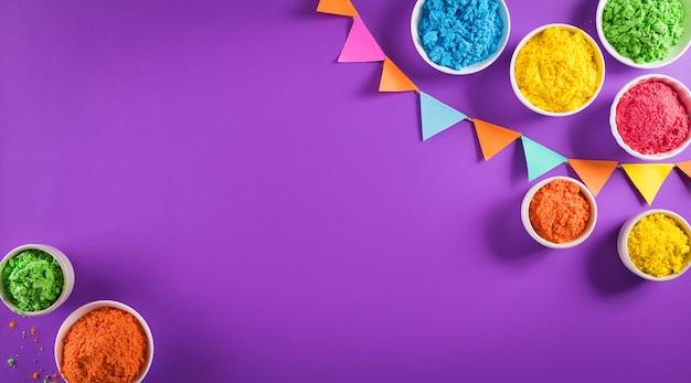 행복 한 holi 축제 장식 보라색 배경에 화려한 holi 분말의 상위 뷰