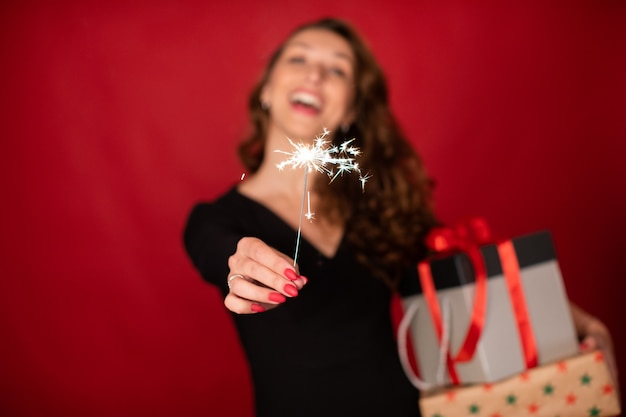 Happy holiday celebration concept. laughing woman holding christmas gifts and burning sparkler in foreground in focus on red background. new year's eve, birthday, awards party concept. copy text space