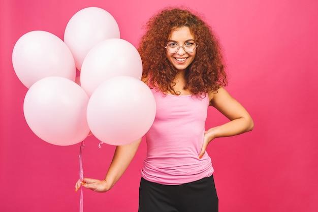 ハッピーホリデー!風船と幸せな若い巻き毛の笑顔の女性