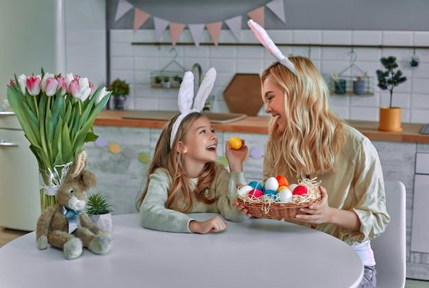 해피 홀리데이! 어머니와 그녀의 딸 그림 계란입니다. 부활절을 준비하는 가족. 귀여운 작은 아이 소녀 토끼 귀를 입고있다.