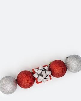 흰색 바탕에 반짝이는 빨간색과 은색 크리스마스 공과 작은 선물 상자가 있는 해피 홀리데이 새해 개념