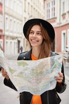 Happy holidaymaker searches right direction on map, explores new town with many sights