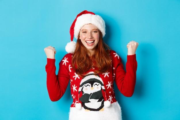 幸せな休日とクリスマスのコンセプト。サンタの帽子とクリスマスセーターを着た陽気な赤毛の女の子、勝利と勝利を祝い、満足して手を挙げ、勝利を収めました。